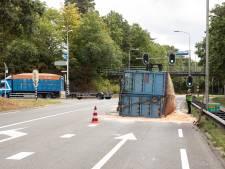 Container vol zaagsel valt van vrachtwagen bij Den Dolder