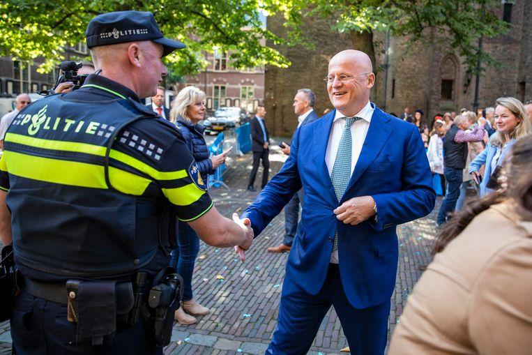 Minister van Justitie en Veiligheid Ferdinand Grapperhaus schudt de hand van een agent voor aanvang van de wekelijkse ministerraad. Beeld Hollandse Hoogte