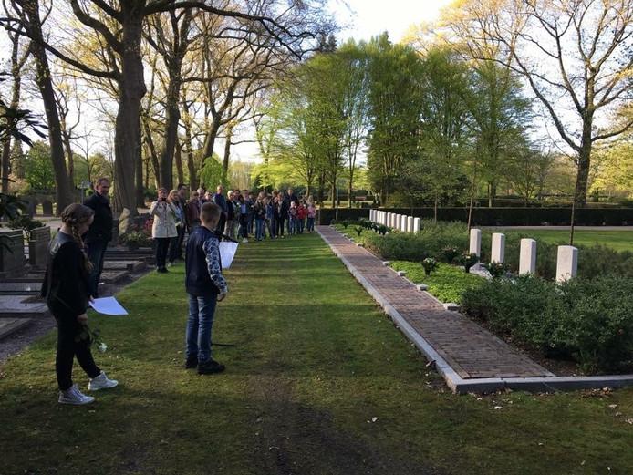 Leerlingen van De Es bij een herdenking op de algemene begraafplaats in hun dorp.