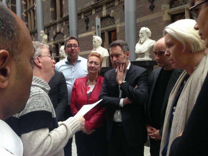 Alex de Vos (tweede van links) biedt tweede kamercommissie zijn visiedocument over de uitvoering van het VN-verdrag aan.