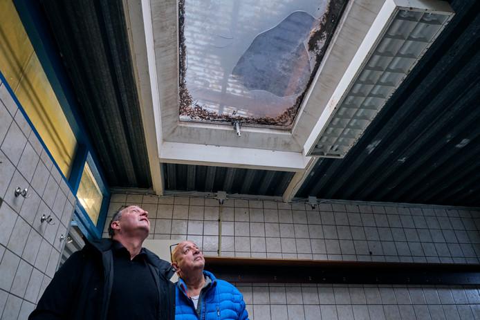 Bestuurslid André van Dijk (links) en Rob Hasselmeijer van de kantinecommissie bekijken het lekkende dak in de kleedkamer.