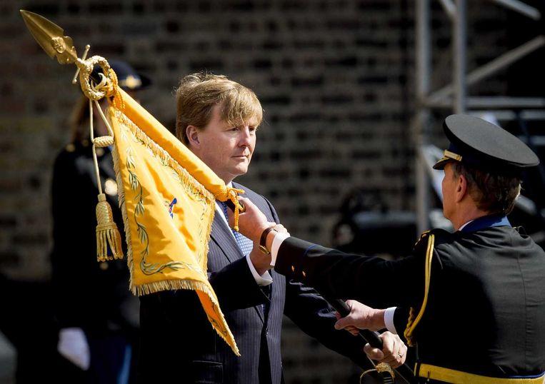 Korpschef Gerard Bouman van de nationale politie krijgt een nieuwe koninklijke standaard uitgereikt door koning Willem-Alexander. Beeld anp