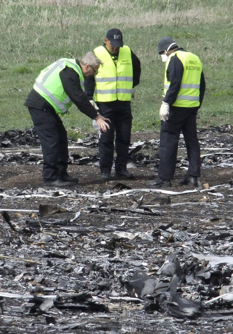 Onderzoekers aan het werk op de plek waar MH17 neerstortte. Beeld reuters