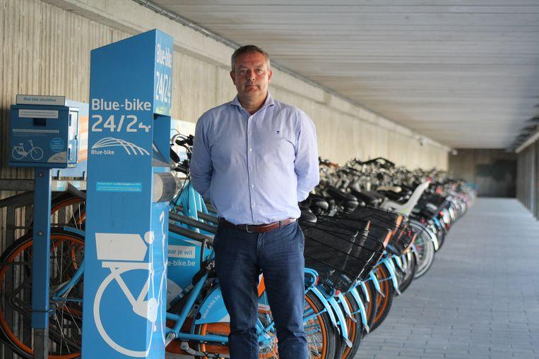 Schepen van Mobiliteit Philip Himpe bij de bestaande deelfietsen aan het station.