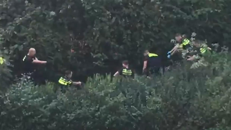 Agenten staan om de man heen na het schietincident. Beeld Screenshot