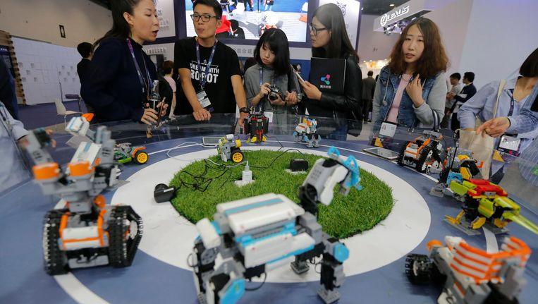 Bezoekers bekijken robots op de Global Mobile Internet Conference (GMIC) exhibition in Beijing, China eind april dit jaar Beeld epa