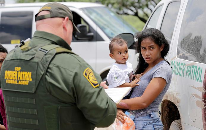 Een vrouw die illegaal de Amerikaanse grens is overgestoken praat met een agent.