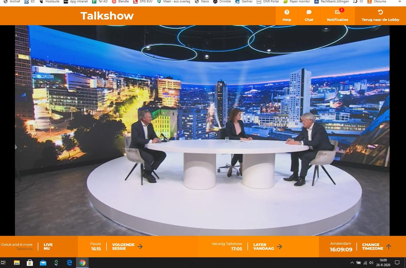 Robert-Jan Smits (l) van TU/e, presentator Mariëlle Tweebeeke en topman Peter Wennink van ASML tijdens Dutch Transformation Forum 2020 in een decor met de Eindhovense skyline.