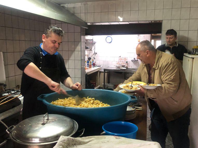 De Bosnische restauranteigenaar Asim Latic (man in kaki jasje) en de kok van de pizzeria in Velika Kladusa maken elke dag een gratis warme maaltijd voor migranten Beeld Thijs Kettenis