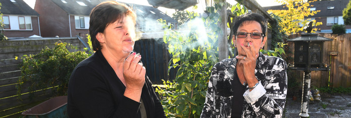 Vianen Buren op de foto Angelique Blok en Dicky ter Schegget (bril) roken samen een peuk over de schuttingFoto William Hoogteyling