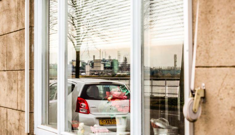 Een weerspiegeling in het raam van een van de huizen in Sliedrecht tegenover Dupont/Chemours aan de andere kant van het Merwedekanaal. Beeld Freek van den Bergh / de Volkskrant