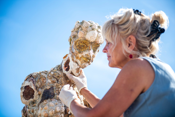 Mariëlle Osté plaatst het hoofd terug op het beeld van de Zwingodin, maar de arm met telefoon komt niet terug.