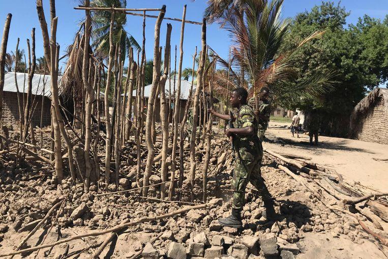 Een soldaat in Mozambique sloopt de resten van een gebouw dat door IS-aanvallers in brand was gestoken. Beeld AFP