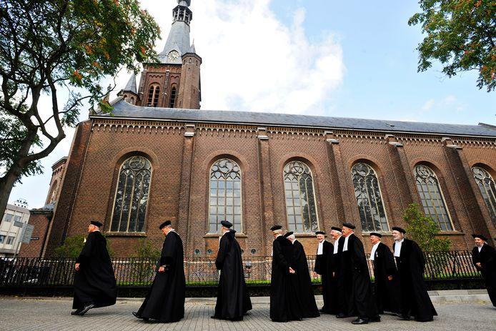 Professoren wandelen langs de Heikese kerk in Tilburg tijdens de opening van het academische jaar in 2008.