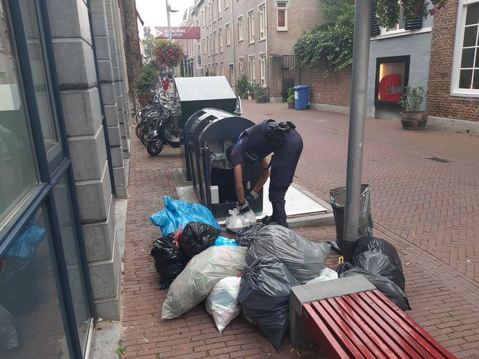Een handhaver van de gemeente controleert in de Kerkstraat in de binnenstad van Arnhem illegaal gedumpte afvalzakken op adresgegevens.