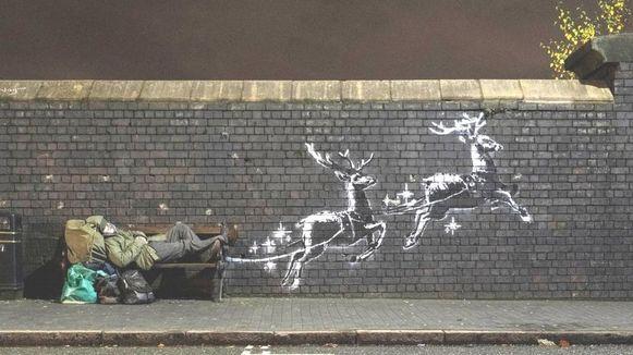 Op de muurschildering trekken twee rendieren een dakloze op een bank mee.