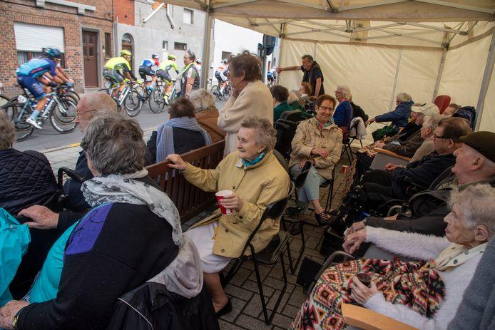 Bewoners van WZC Kouterhof supporteren voor het voorbijrazende peloton.