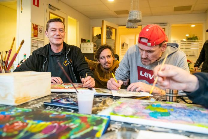 Henk Kisjes (links) en Jeroen Spoelman (midden) aan tafel met een van de deelnemers van de kunst dagbesteding van Tactus Verslavingszorg in Zwolle.