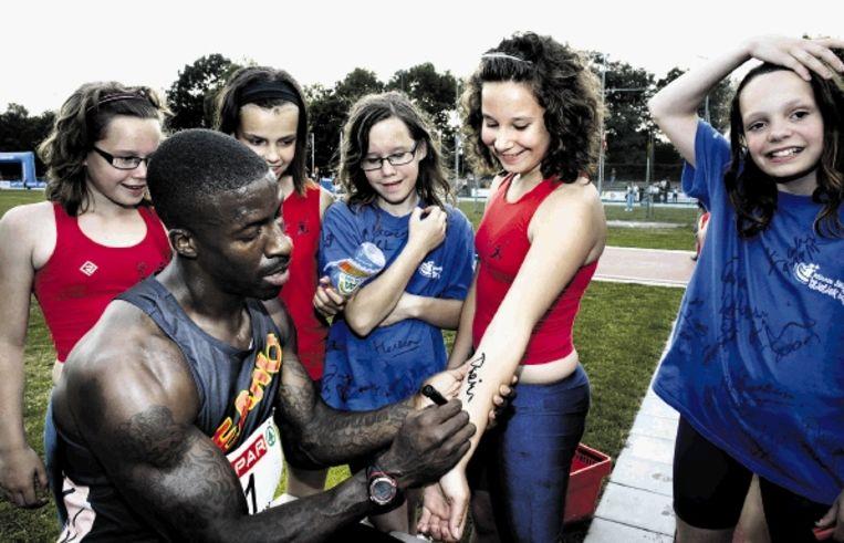 Dwain Chambers deelt in Uden tussen de bedrijven door handtekeningen uit aan jeugdige fans. (FOTO DOLPH CANTRIJN) Beeld