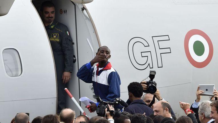 Eén van de Eritrese vluchtelingen betreedt onder toeziend oog van de Italiaanse pers het vliegtuig naar Zweden. Beeld afp