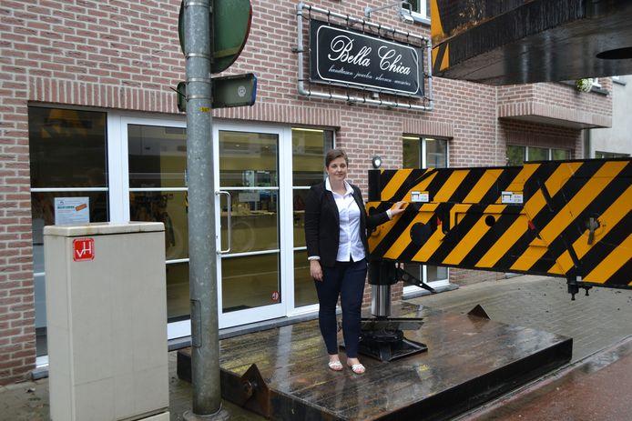 Tatiana Wouters aan haar winkel. De houten constructie en de gigantische bouwkraan werden op amper een halve meter van de inkomdeur geplaatst.