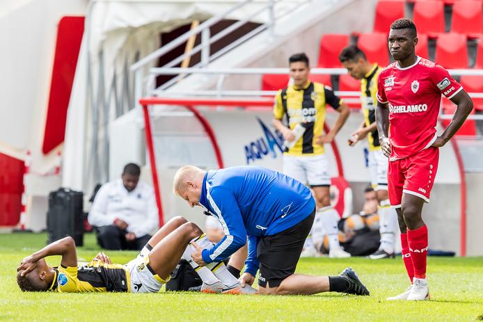 Charly Musonda grijpt naar zijn hoofd van pijn, nadat hij een zware blessure heeft opgelopen in zijn eerste optreden voor Vitesse.  Fysiotherapeut Jos Kortekaas verzorgt de Belg.
