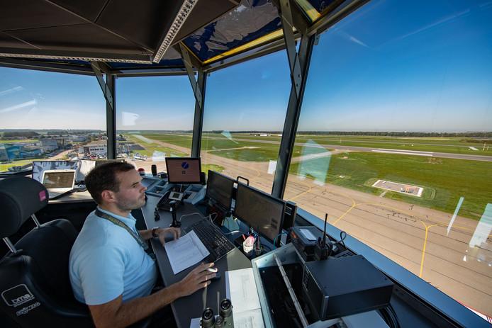 Een luchtverkeersleider kijkt vanuit de verkeerstoren naar de start- en landingsbaan op Lelystad Airport.