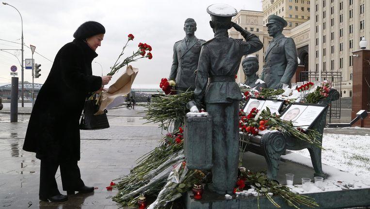 Vrouw legt bloemen neer bij de portretten van de omgekomen Russische soldaten Beeld epa
