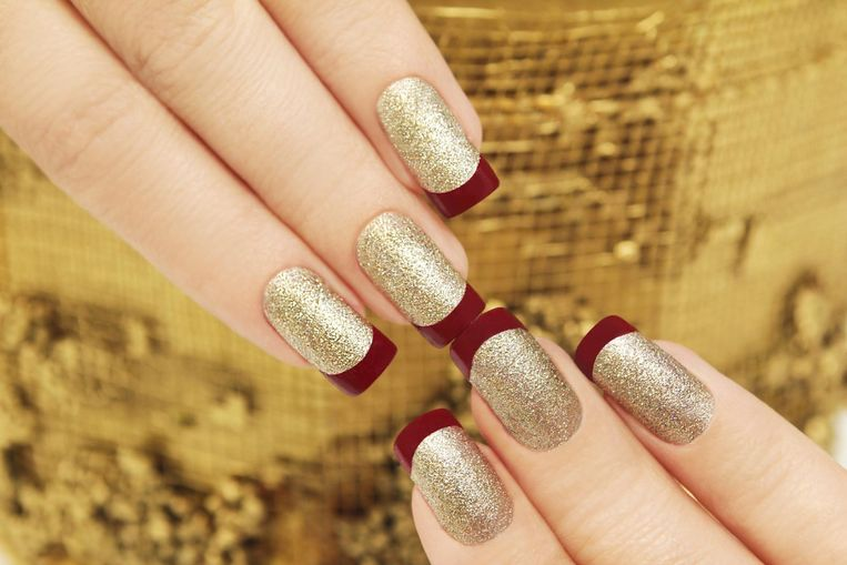 French manicure, maar dan met rood en glittergoud Beeld Shutterstock