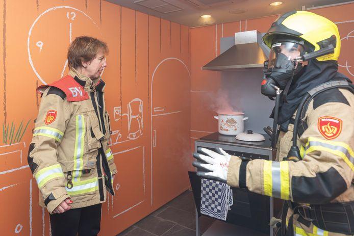 Burgemeester Margo Mulder van Goes en een brandweerman demonstreren in de pop-up store wat je kan doen als de vlam in de pan slaat.