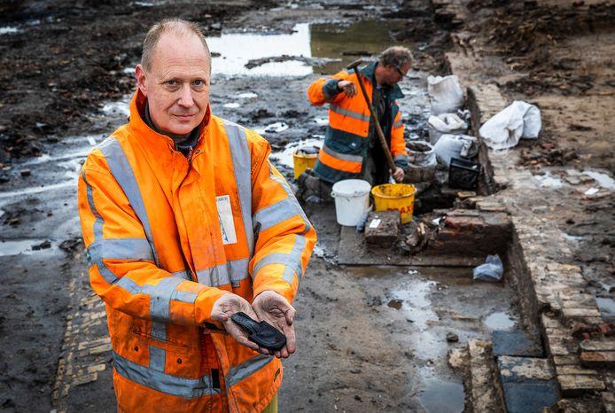Archeoloog Jeroen Ras met het gevonden kinderschoentje uit de 17de eeuw.