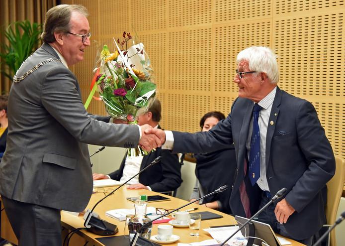 Raadslid Dick Oggel (rechts) krijgt bloemen van burgemeester Jan Lonink.
