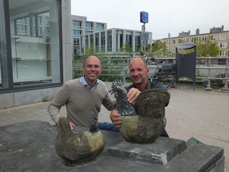 Schepen Bruno Dhaenens (Open Vld) en kunstenaar Koen Verbrugghe met de nieuwe kippenkop.