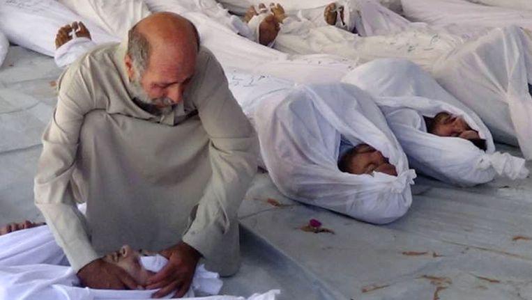 Een man rouwt bij de slachtoffers van de mogelijke gifgasaanval in Syrië. Beeld ap