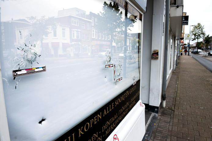 De kogelgaten zijn goed zichtbaar in het raam van de juwelier op de Amsterdamsestraatweg.