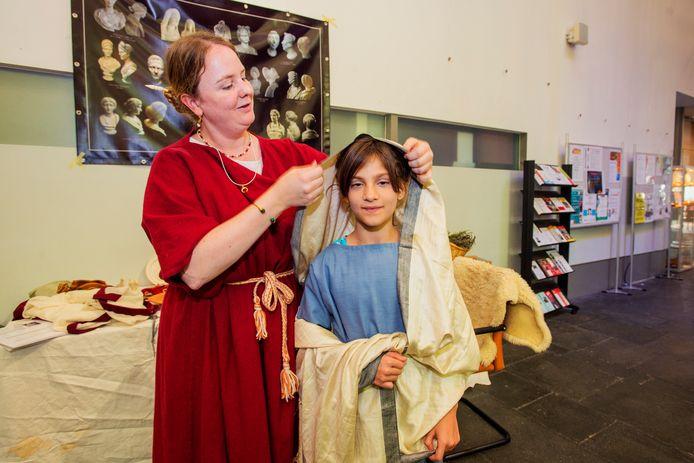 De 9-jarige Eva Gedö uit Tilburg wordt door Martine Teunissen op z'n Romeins aangekleed.