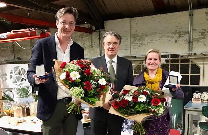 Joks Jansen (links) en Mijntje Notermans (rechts) ontvangen hun commissarispenning van Wim van de Donk (midden).