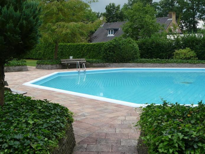 Het zwembad van Dennenoord met daarachter het (tijdelijke) gezinshuis voor autistische kinderen.