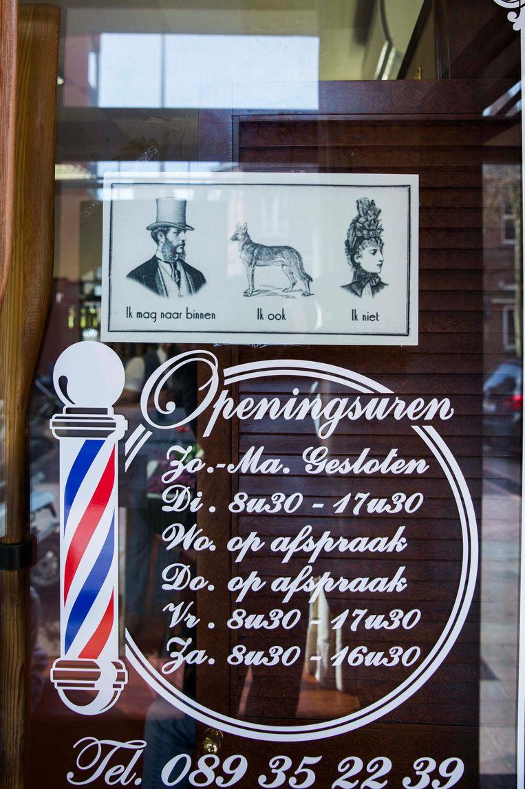 """Het nieuwe bord, dat aan de deur van barbier Cesar hangt. Het vermeldt dat mannen en honden naar binnen mogen, maar vrouwen niet. """"Een ludieke actie"""", vindt de barbier. """"Discriminatie"""", zeggen enkele buren."""