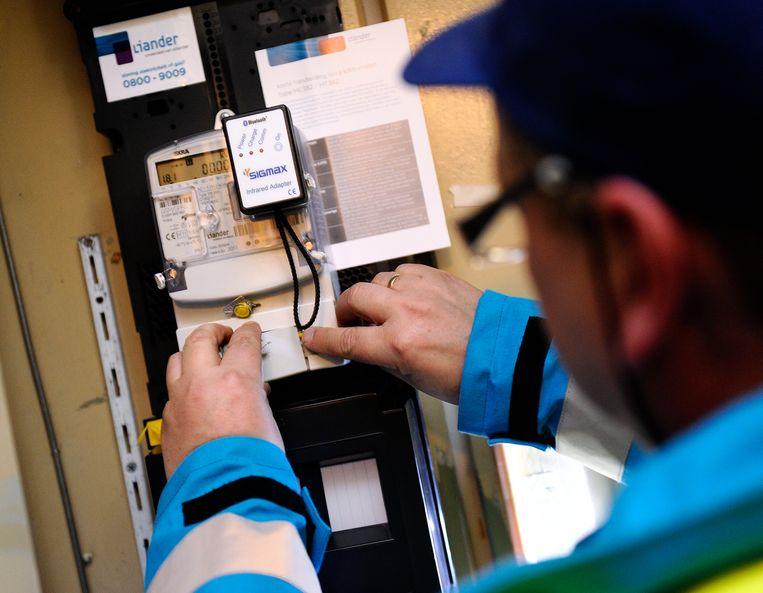 Een monteur verricht werkzaamheden aan een energiemeter.  Beeld ANP