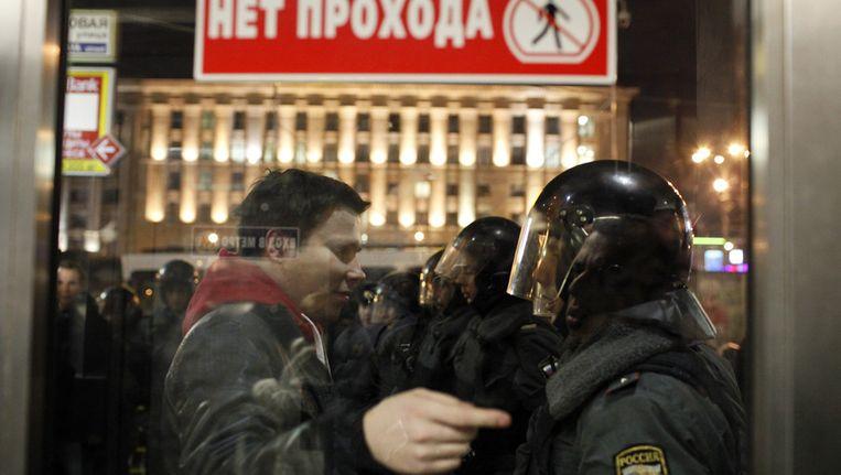 Een betoger en een veiligheidsagent in Moskou, gisteren. Beeld ap