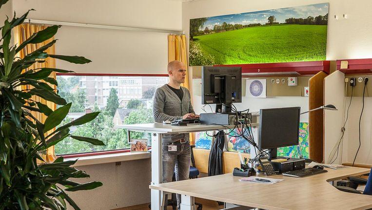 Istvan Haarman aan zijn werktafel in Enschede: 'Sinds ik sta, voel ik me veel frisser en energieker.' Beeld Harry Cock / de Volkskrant
