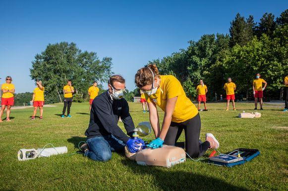 Karel Logge toont hoe een beademingsmasker met 2 handen omklemd moet worden terwijl een collega afwisselend hartmassage geeft en de beademingspomp bedient