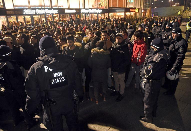 Duitse agenten drijven een groep mannen samen voor het treinstation in Keulen, op oudejaarsavond 2016. Dat doen ze na de massale aanrandingen een jaar eerder, waarbij vooral Noord-Afrikanen vrouwen lastigvielen.