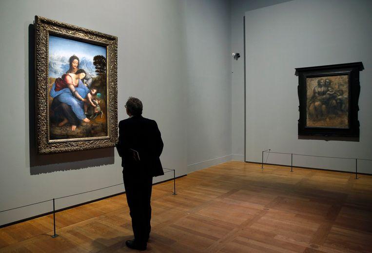Bezoeker tijdens de persbezichtiging van de tentoonstelling Léonard de Vinci in het Louvre voor het schilderijMaria met kind en Sint Anna, gemaakt door Da Vinci tussen 1503 en 1519. Beeld Getty