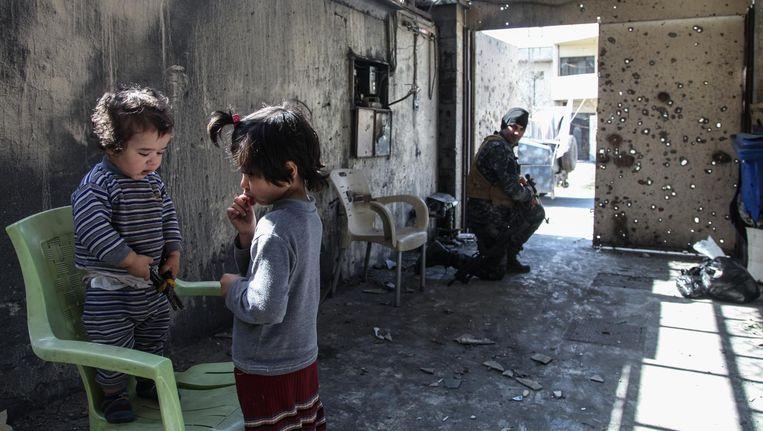 Een militair bewaakt een huis en de kinderen die er wonen, in West-Mosul. Beeld Jana Andert