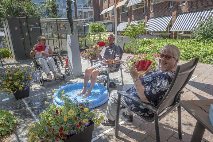 Ouderen van Humanitas met ijs bij een opblaasbadje.