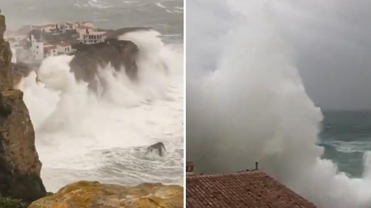 Storm blaast golven metershoog over huizen op rots