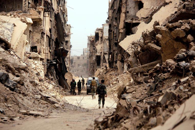 Militairen lopen door een gebombardeerde straat in het vluchtelingenkamp Yarmouk in de Syrische hoofdstad Damascus.   Beeld REUTERS
