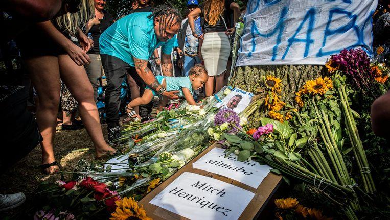 Deelnemers aan een stille tocht voor Mitch Henriquez leggen bloemen en spandoeken neer in het Zuiderpark, een week na zijn arrestatie op 27 juni 2015. Beeld Robin Utrecht